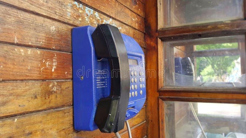 caja de llamada de madera con el teléfono azul imagen de archivo libre de regalías