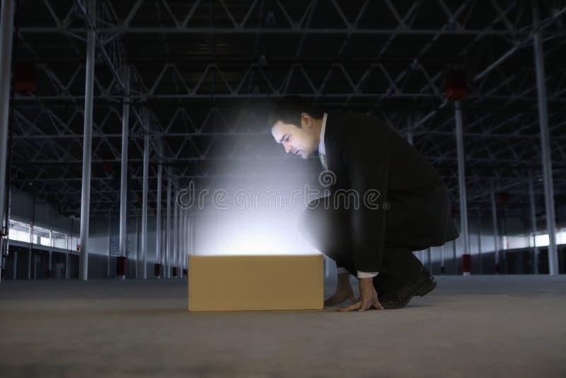 Caja de Looking At Glowing del hombre de negocios en Warehouse vacío fotos de archivo libres de regalías
