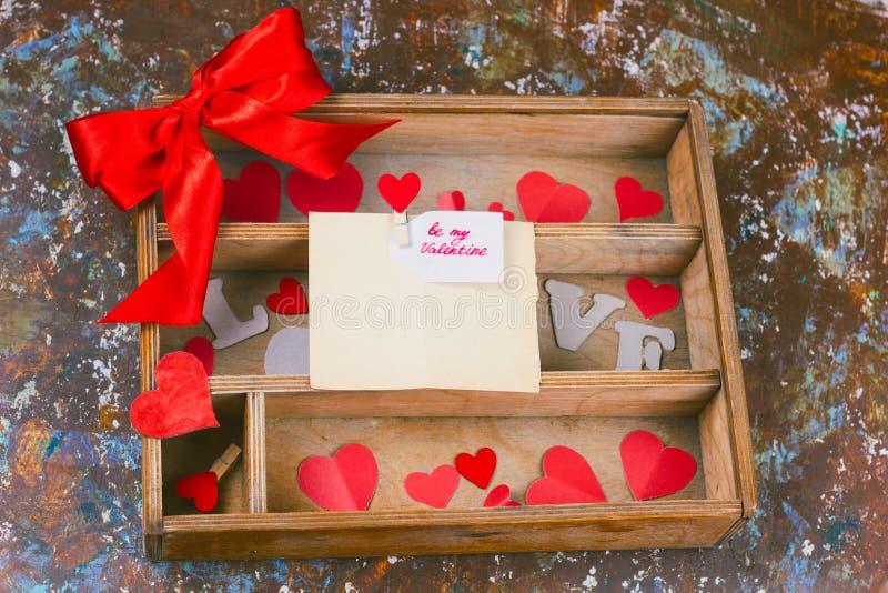 Caja de madera con los corazones de papel y presentar con el arco y el lavel rojos con ser mi nota de la tarjeta del día de San V fotos de archivo libres de regalías