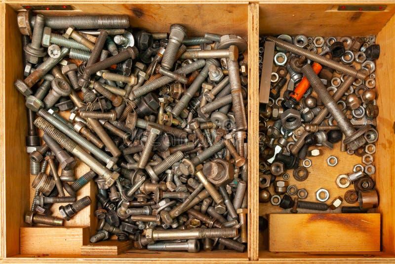 Caja de madera con un manojo de nueces, de pernos y de tornillos foto de archivo libre de regalías