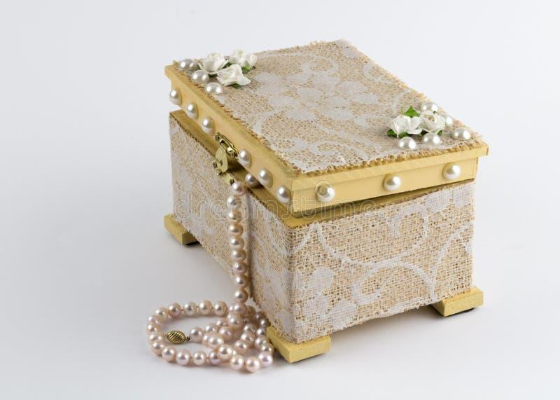 Caja de madera de los Arty con el collar de la perla aislado en el fondo blanco fotos de archivo