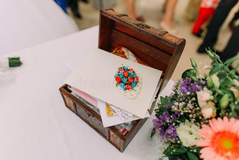 Caja de madera para casarse sobres del dinero en la tabla adornada por las flores coloridas imagenes de archivo