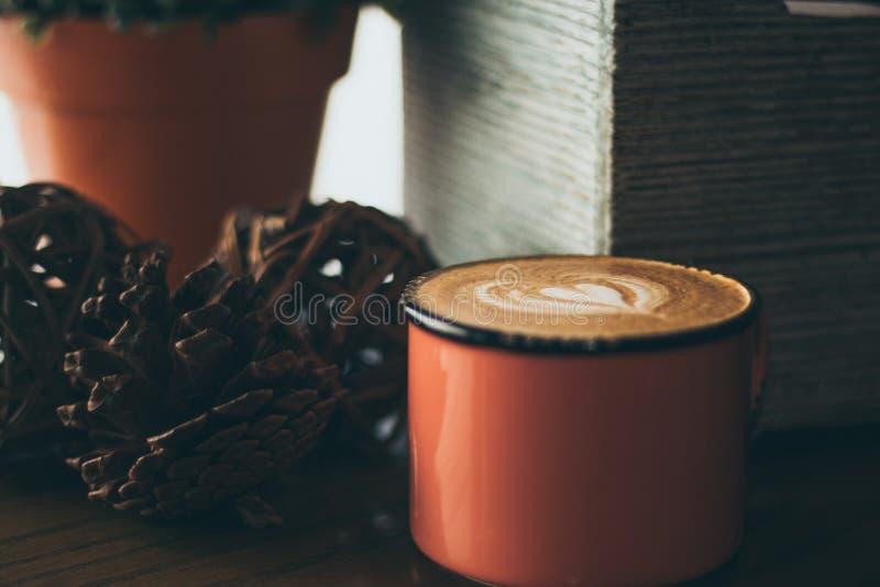 Caja de madera y latte en una taza roja fotografía de archivo
