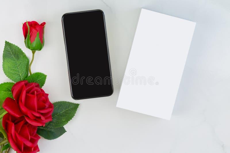 Caja de nuevo teléfono de Smartphone al lado de rosas rojas en el backgrou de mármol imagen de archivo libre de regalías