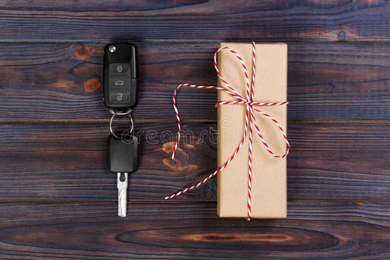 Caja de papel cercana dominante del coche con el arco rojo de la cinta en fondo de madera de la tabla Regalo del día del ` s de l foto de archivo