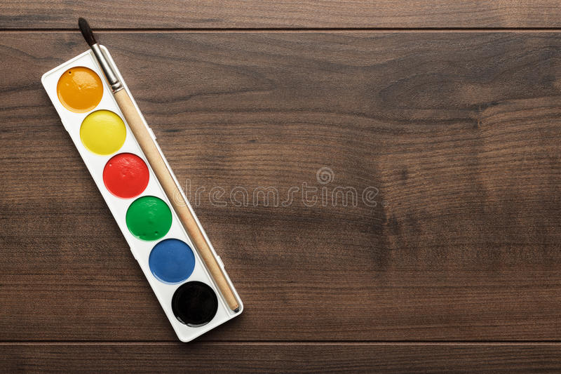 Caja de pinturas y un cepillo en la tabla imagen de archivo libre de regalías