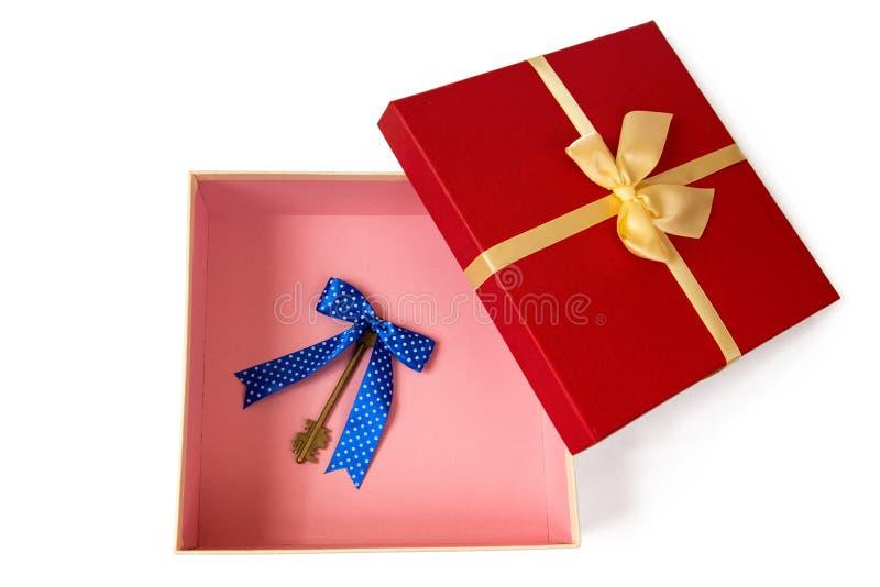 Caja de regalo abierta con el arco de la cinta del oro y llaves del vintage con el arco azul dentro foto de archivo libre de regalías