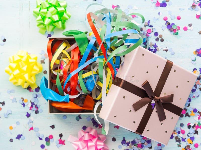 Caja de regalo abierta con las flámulas y el confeti del partido fotos de archivo