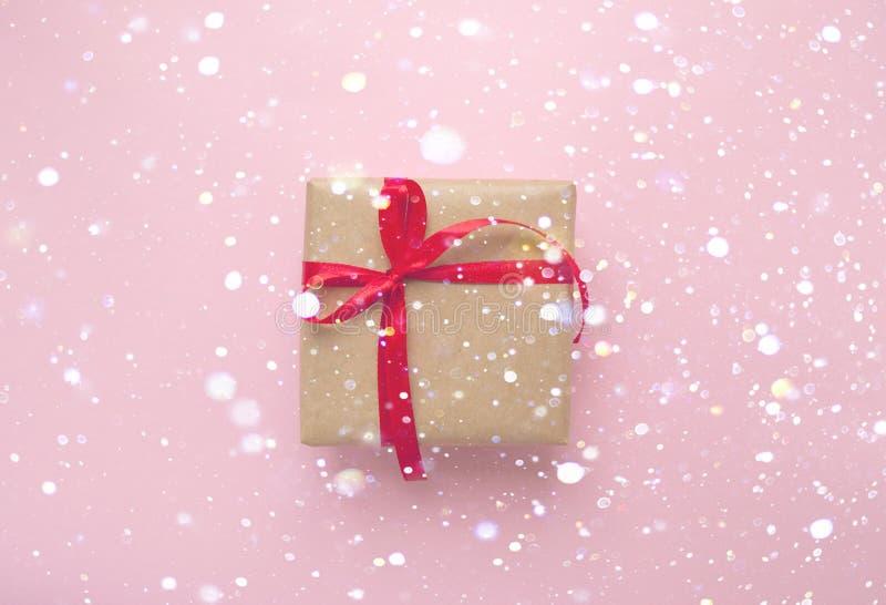 Caja de regalo atada con la cinta roja en fondo rosado en colores pastel fotos de archivo libres de regalías