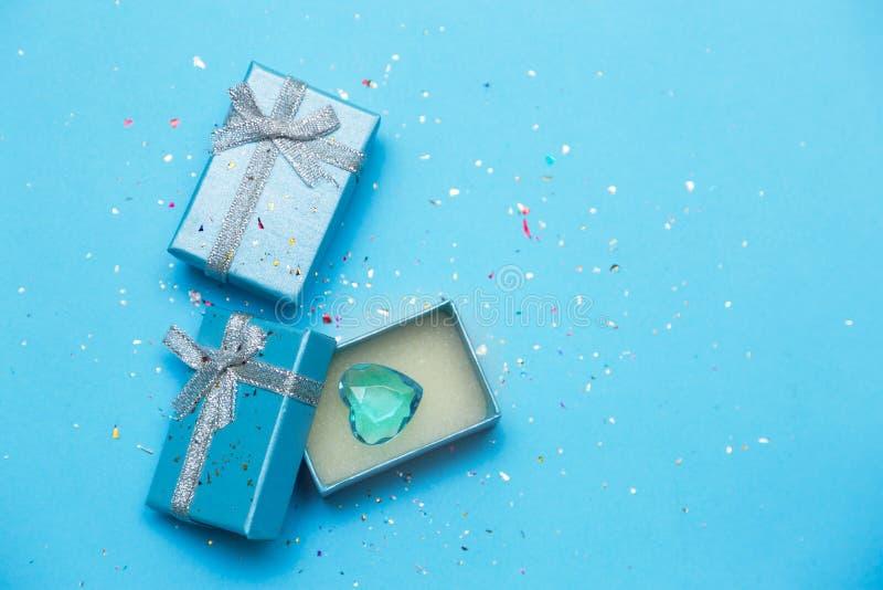 Caja de regalo azul con joyería y el corazón cristalino Fondo para una tarjeta de la invitaci?n o una enhorabuena fotos de archivo