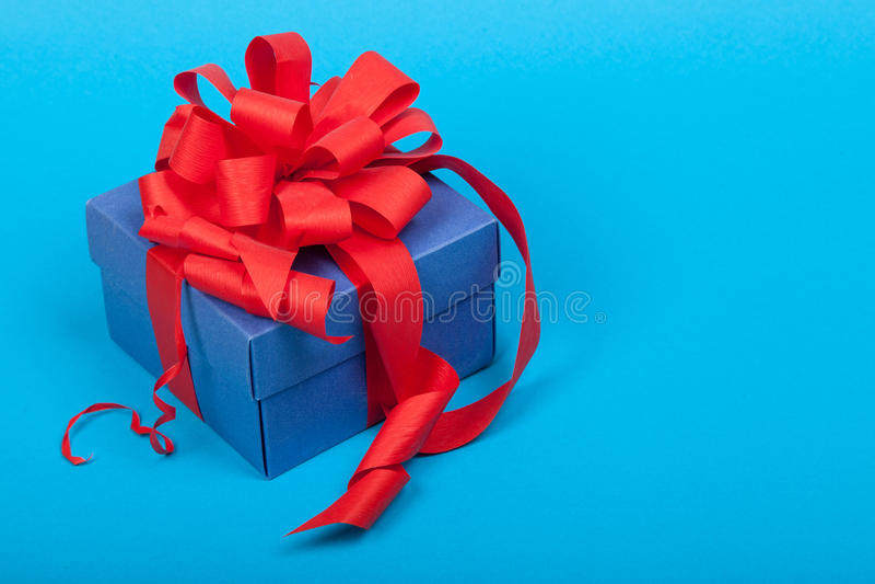 Caja de regalo azul con la cinta roja y arco en fondo azul imágenes de archivo libres de regalías