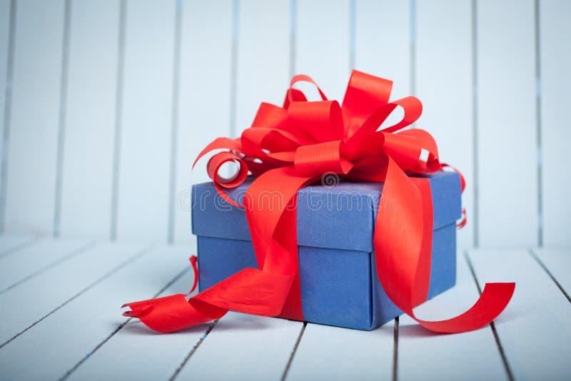 Caja de regalo azul con la cinta roja y arco en fondo azul brillante foto de archivo