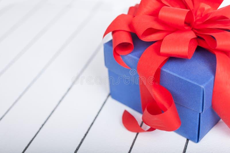 Caja de regalo azul con la cinta roja y arco en fondo de madera imagenes de archivo