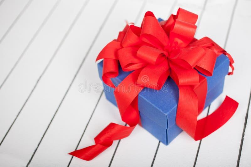 Caja de regalo azul con la cinta roja y arco en fondo de madera fotografía de archivo