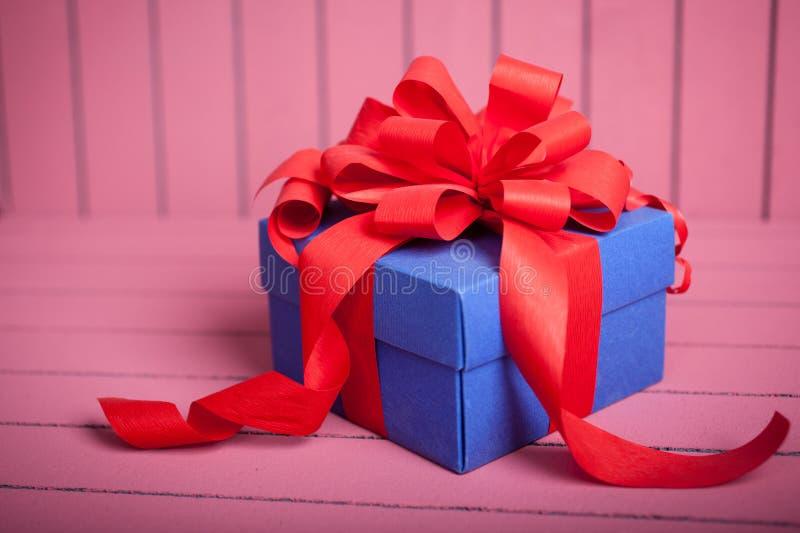 Caja de regalo azul con la cinta roja y arco en fondo rosado imagenes de archivo