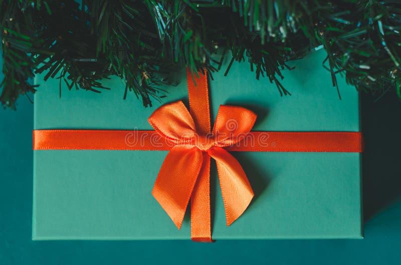 Caja de regalo azul con un cierre anaranjado de la rama del arco y de árbol de navidad encima de la visión superior fotos de archivo