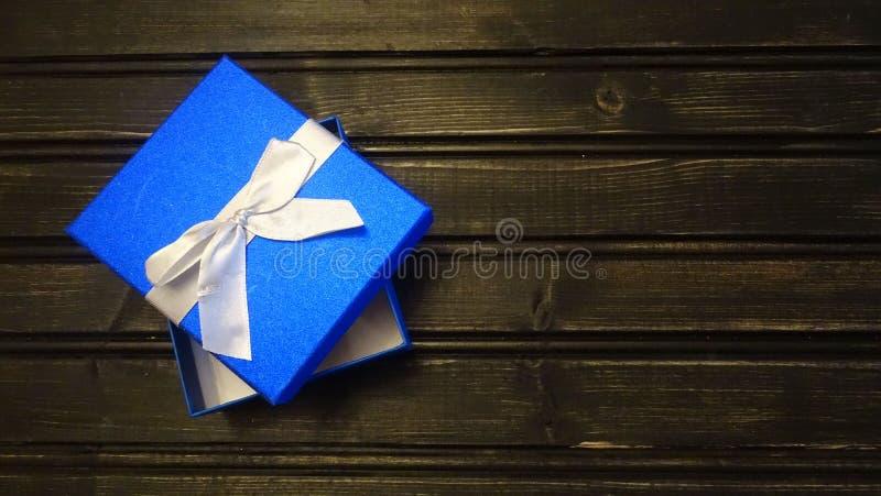 Caja de regalo azul con un fondo de madera foto de archivo
