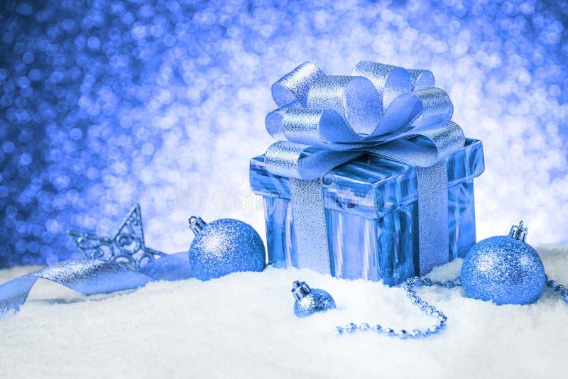 Caja de regalo azul de la Navidad con las bolas y decoración en nieve foto de archivo