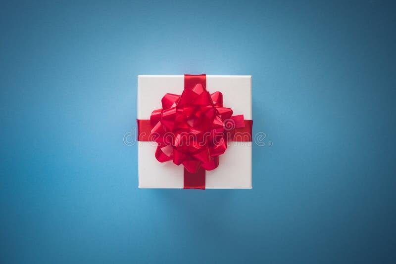 Caja de regalo blanca con el lazo de satén rojo y cinta en la parte posterior en colores pastel del azul fotografía de archivo