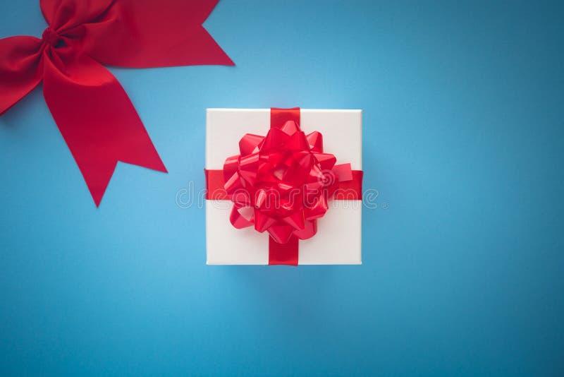 Caja de regalo blanca con el lazo de satén rojo y cinta en la parte posterior en colores pastel del azul foto de archivo
