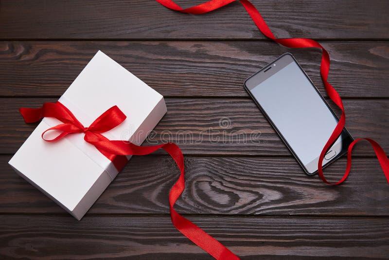 Caja de regalo blanca con la cinta roja y smartphone en un fondo de madera foto de archivo