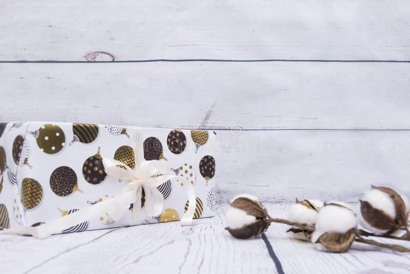 Caja de regalo blanca con las bolas pintadas de la Navidad, rama del algodón en el wo foto de archivo