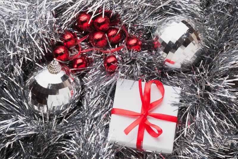 Caja de regalo blanca con un arco rojo en la guirnalda de plata foto de archivo