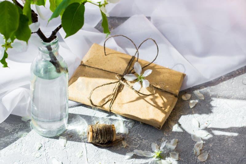 Caja de regalo bonita envuelta con el papel marrón del arte y adornada con el yute imagen de archivo