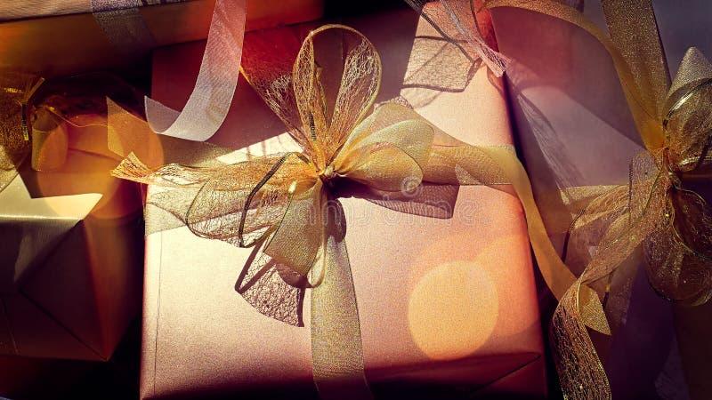 Caja de regalo brillante del oro con las cintas fotos de archivo