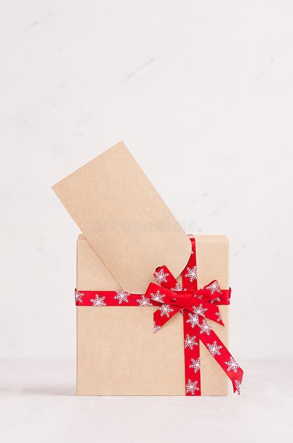 Caja de regalo brillante rica de papel de Kraft con la cinta roja y de primer en blanco de la tarjeta de felicitación en la tabla imagen de archivo libre de regalías