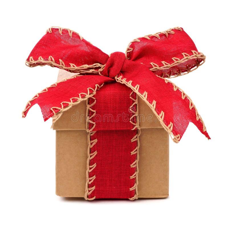 Caja de regalo de Brown con el arco rojo y cinta aislada en blanco imagenes de archivo