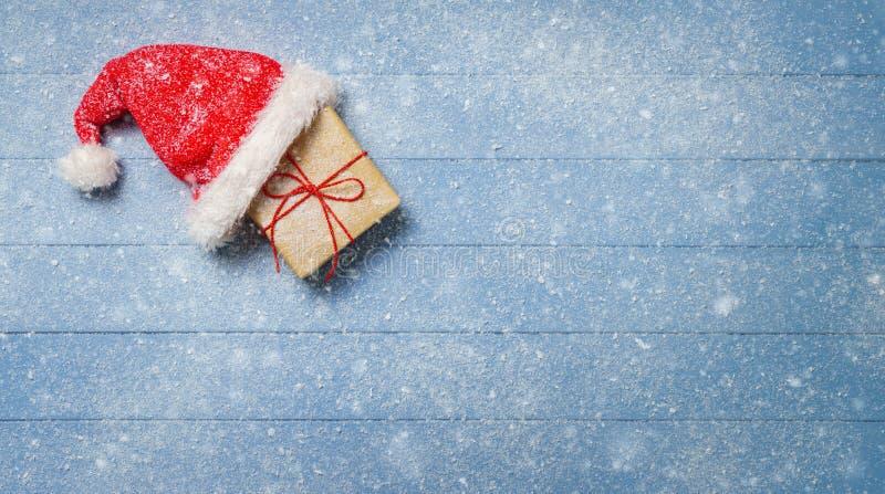Caja de regalo de Brown con el sombrero de santa en la tabla de madera azul cubierta con la nieve - panorama imagenes de archivo