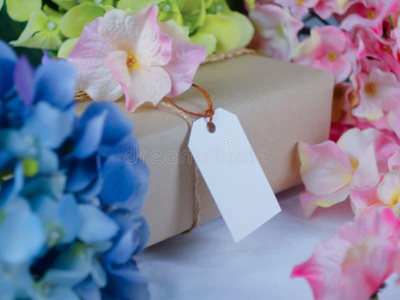 Caja de regalo de Brown con las etiquetas de papel en blanco y colocada en medio de las flores azules y rosadas fotografía de archivo