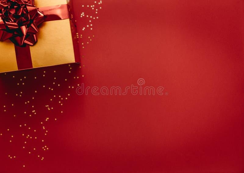 Caja de regalo coloreada de oro con las estrellas en fondo rojo imágenes de archivo libres de regalías