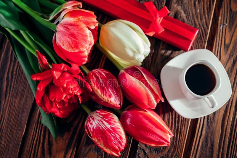 Caja de regalo con café y tulipanes frescos en fondo de madera Sorpresa de la mañana Buenos días imagenes de archivo
