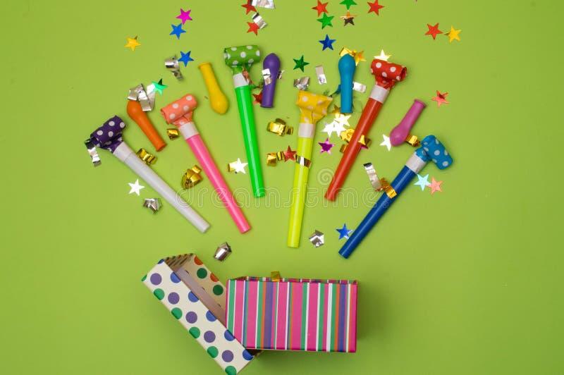 Caja de regalo con confeti, globos, flámulas, los noisemakers y la decoración del diverso partido en un fondo verde colorido imágenes de archivo libres de regalías