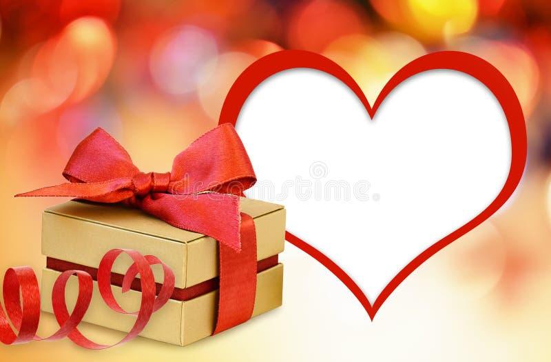 Caja de regalo con el arco de la cinta y la tarjeta rojos de la forma del corazón fotos de archivo