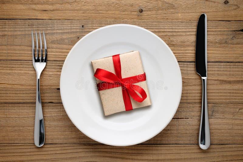 Caja de regalo con el arco rojo en la placa fotos de archivo libres de regalías