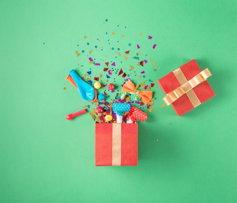 Caja de regalo con el confeti del partido, globos, flámulas, noisemakers fotografía de archivo libre de regalías