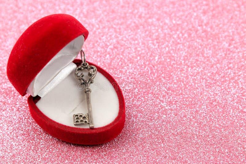 Caja de regalo con el primer dominante en un fondo rosado brillante brillante Día del `s de la tarjeta del día de San Valentín Es imagen de archivo