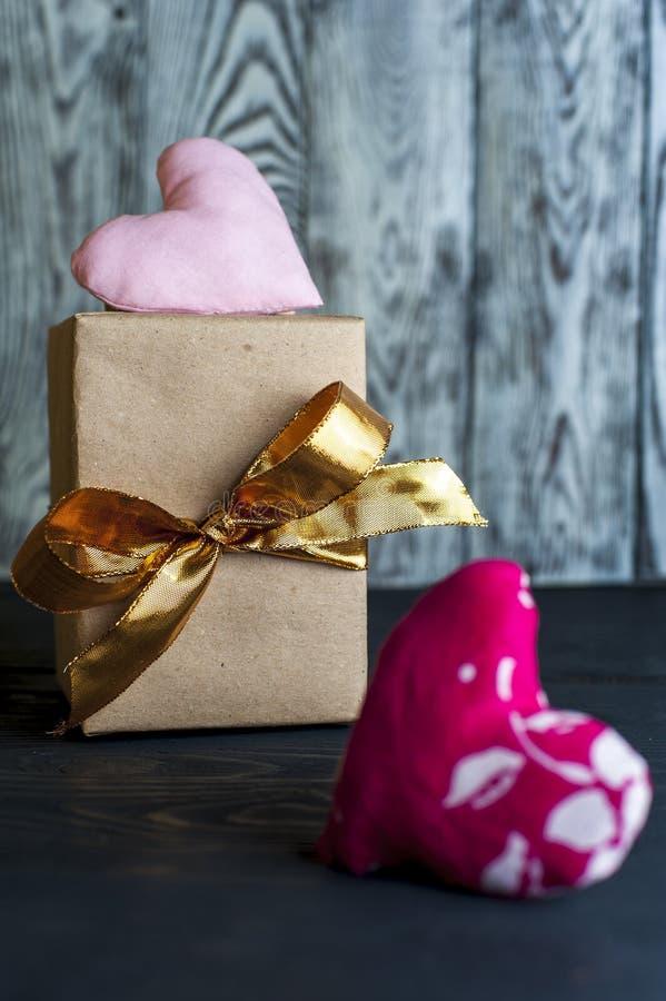Caja de regalo con la cinta de oro y el corazón hecho a mano imagenes de archivo