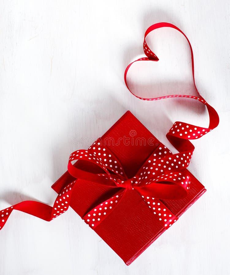 Caja de regalo con la cinta roja del arco en el fondo blanco para día de San Valentín fotos de archivo