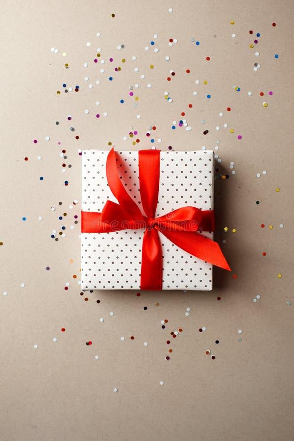 Caja de regalo con la cinta roja y confetty en fondo gris Día de la madre de tarjeta del día de San Valentín, venta, compras, par fotos de archivo libres de regalías