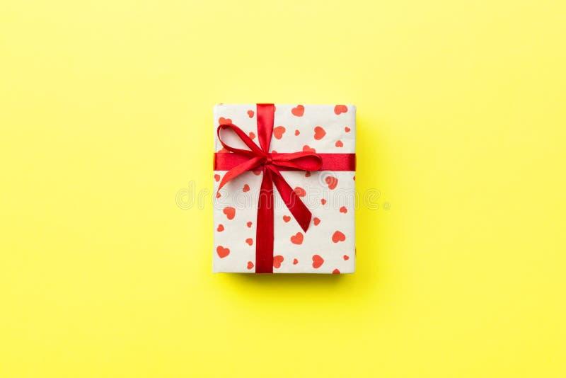 Caja de regalo con la cinta roja y corazón en el fondo amarillo, visión superior con el espacio de la copia para el texto imagen de archivo