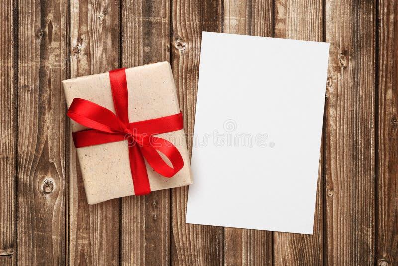 Caja de regalo con la cinta roja y la tarjeta de felicitación en blanco foto de archivo