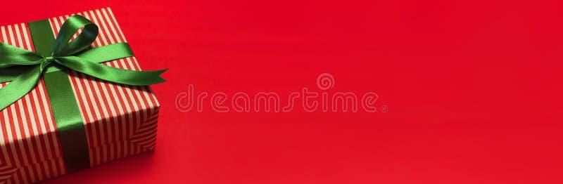 Caja de regalo con la cinta verde en endecha roja del plano de la opinión superior del fondo Concepto del día de fiesta, regalo d imágenes de archivo libres de regalías