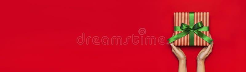 Caja de regalo con la cinta verde en manos femeninas en endecha plana roja de la opinión superior del fondo Año Nuevo del concept imagenes de archivo