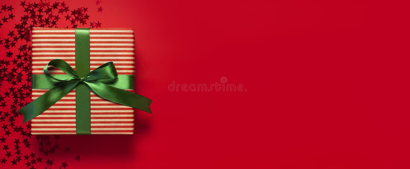 Caja de regalo con la cinta verde y la forma olográfica del confeti del brillo de estrellas en endecha plana roja de la opinión s foto de archivo