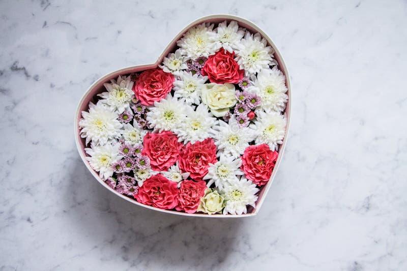 Caja de regalo con las flores en forma de corazón en fondo de mármol gris fotografía de archivo libre de regalías