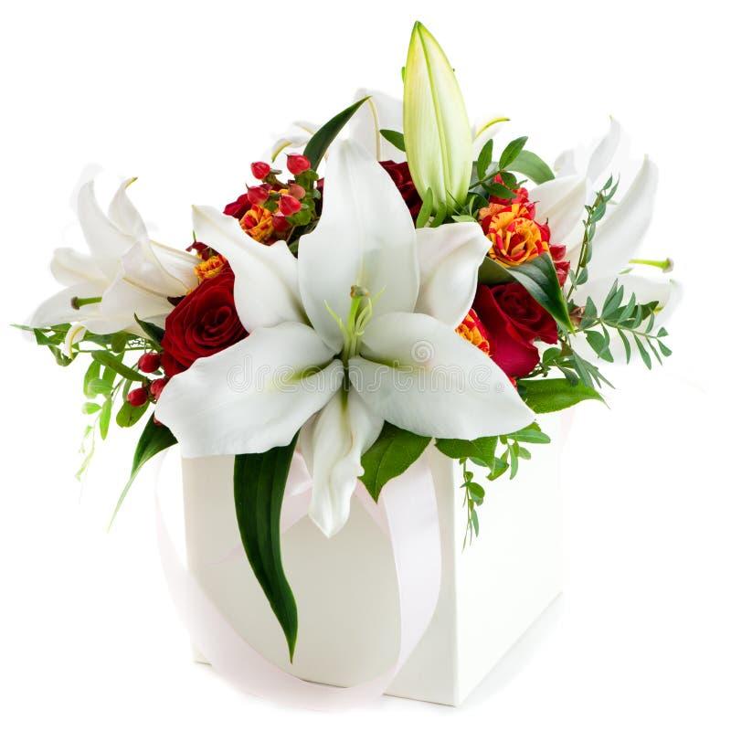 Caja de regalo con las flores frescas del lirio y crisantemo aislado en w foto de archivo libre de regalías